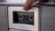 istock Open Cassette Deck of Old Tape Recorder, Insert 90s Cassette, Close with Fingers 1304268661