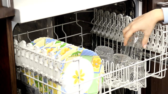 Open dishwasher with clean utensils in it. video