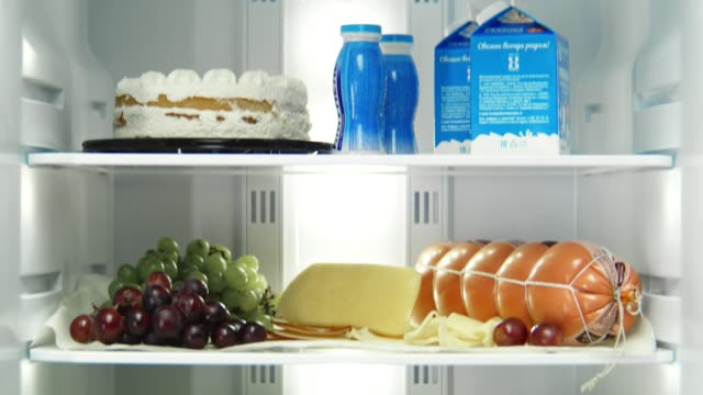 open domestic fridge with different products on shelves - deser filmów i materiałów b-roll