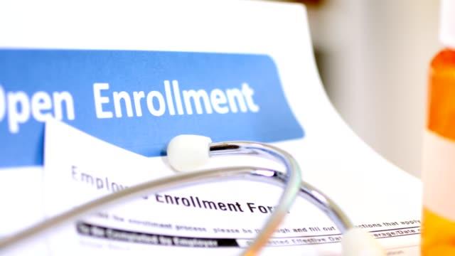vídeos de stock e filmes b-roll de open enrollment healthcare benefit forms. - benefits