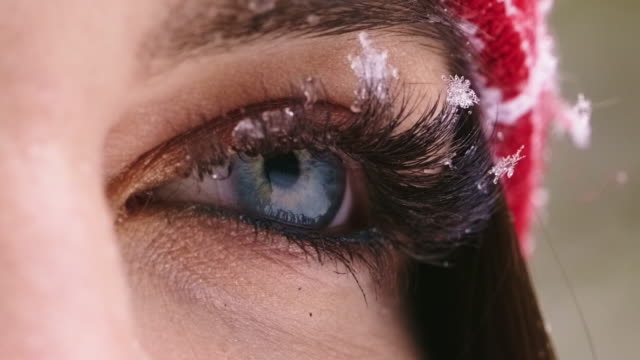 Open expressive blue eyes with frost or snow on eyelashes macro close-up in winter. video
