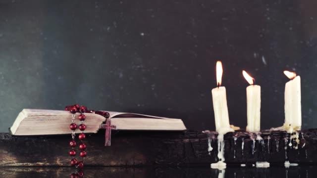 stockvideo's en b-roll-footage met open bijbel en kaarsen op een oude houten verbrande tabel. mooie donkere achtergrond. religieuze concept. - halsketting
