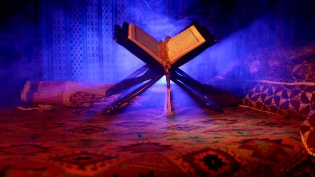 stockvideo's en b-roll-footage met open heilige boek van moslims op stand op oost-tapijt met donker getinte mistige achtergrond. islamitische godsdienst concept. selectieve aandacht. schuifregelaar geschoten. - heilig geschrift