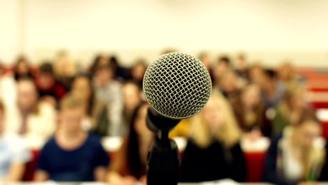 Open microphone with blurred people behind Stock HD video clip footage of a room full of people focussing on a Microphone at the front presentation speech stock videos & royalty-free footage