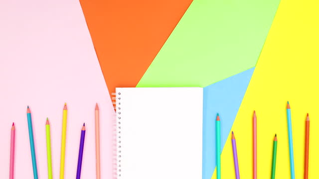 Open notebook and colored pencils appear on bottom of colorful theme. Stop motion