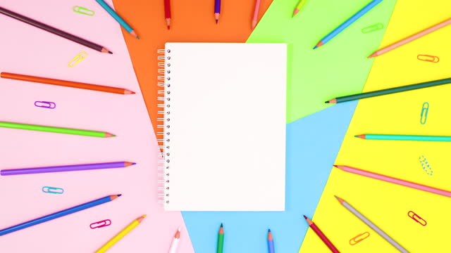 Open notebook and pencils and paper clips appear on colorful theme. Stop motion
