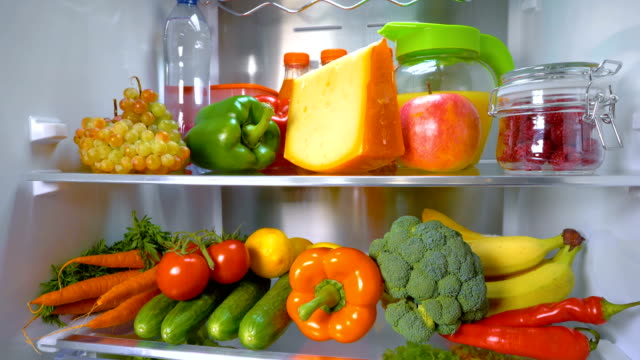 Open refrigerator filled with food Open refrigerator filled with food. Healthy food. fridge stock videos & royalty-free footage