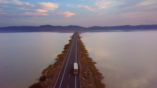 Open road ahead Aerial view of a straight road over a lake in Mexico. Real time video. independence stock videos & royalty-free footage