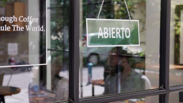 """abierto - schild """"geöffnet"""" in spanischer sprache - schaufenster stock-videos und b-roll-filmmaterial"""