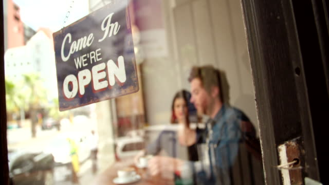 vídeos de stock, filmes e b-roll de sinal de aberto na porta de vidro de café - aberto
