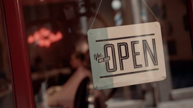 Open signboard on old-fashioned barber shop window with barber indoors video