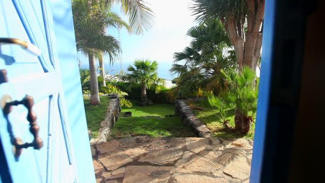 Open the door. Palm trees in a garden. video