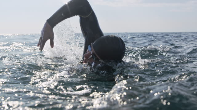SLO MO Open water swimmer at sea swimming front crawl in sunshine Slow motion medium handheld shot of a open water swimmer swimming forward crawl in the sunny sea. Shot in Slovenia. wristwatch stock videos & royalty-free footage