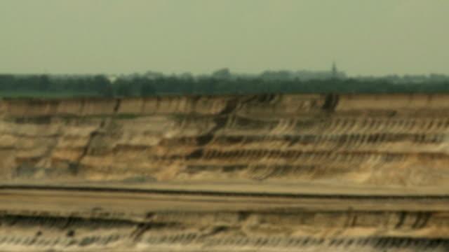 Open-cast mining. Defocus on soil and church. Medium shot. Surface mine. video