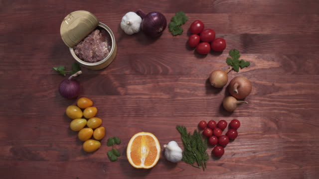 Opened Meat tin can served with vegetables and fruits, top view of a wooden table shot. video