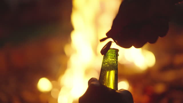 SLOMO POV opening a bottle of beer in front of a bonfire
