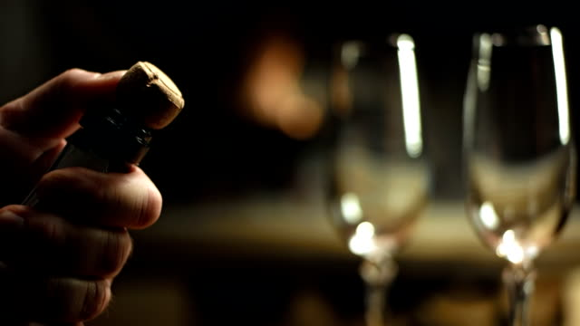 HD: Opening A Bottle Of Champagne HD1080p: Romantic scene of an unrecognizable man opening a bottle of champagne with two glasses and a fireplace in the blurred background. falling in love stock videos & royalty-free footage