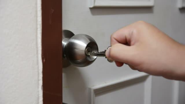 aprire una serratura con chiave - portachiavi video stock e b–roll