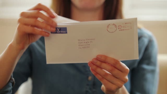 Opening a letter          LI CM RO Dolly shot of a young woman in the home, on a sofa, opening a letter to be pleasantly surprised by the contents. good news stock videos & royalty-free footage