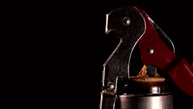 Opening a wine bottle with corkscrew, black background, Winery video