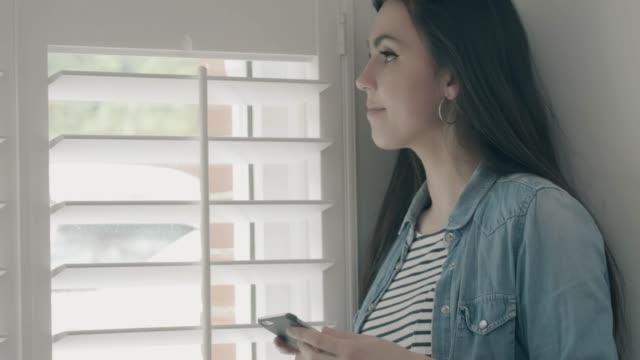 otwieranie żaluzji i używanie telefonu przez okno. - store filmów i materiałów b-roll
