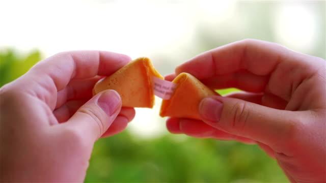 vídeos y material grabado en eventos de stock de abrir galleta de la fortuna china con una tarjeta dentro en cámara lenta 180fps - galleta dulces