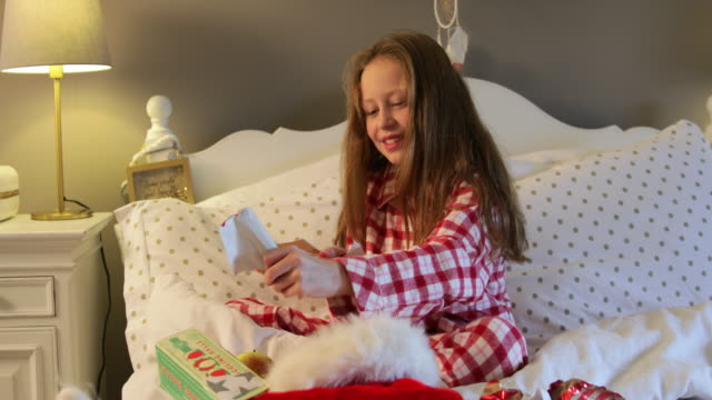 Opening Her Stocking Girl opening a Christmas stocking while sitting in bed on Christmas morning. christmas stocking stock videos & royalty-free footage