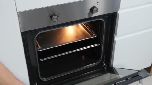 vídeos de stock e filmes b-roll de opening oven in white kitchen witk light. - burned oven