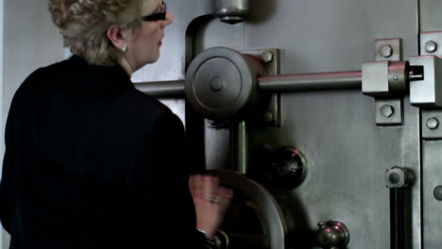 Opening Vault Woman opens a large bank vault door.  Close up. safes and vaults stock videos & royalty-free footage