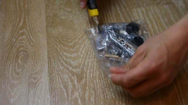 openinig unpacking plastic package full of different fasteners, fittings and fixings for assembly mounting firniture