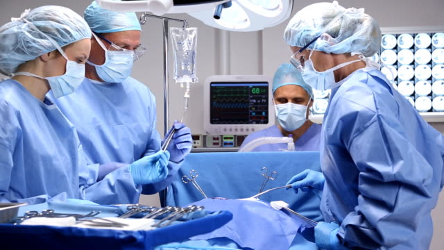 Operating Room HD1080p + NTSC DV, 29.97fps.  Surgical team in operating room.  Camera dolly moves from right to left. operating stock videos & royalty-free footage