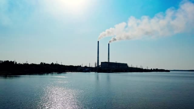 operating thermal power plant in the city. - centrale termoelettrica video stock e b–roll