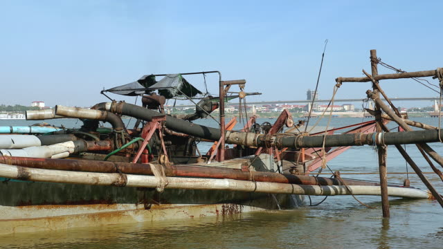operation of pumping sand out of a dredging ship through a pipe hold between bamboo canes. Ship being tied to shore. operation of pumping sand out of a dredging ship through a pipe hold between bamboo canes. Ship being tied to shore. pipe connector stock videos & royalty-free footage