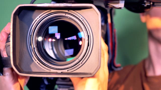 Operator is holding a video camera, turning it thereafter it is zooming out Operator is holding a video camera, turning it thereafter it is zooming out. 4K camera photographic equipment stock videos & royalty-free footage