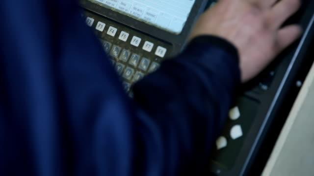 Operator presses button on CNC machine closeup video