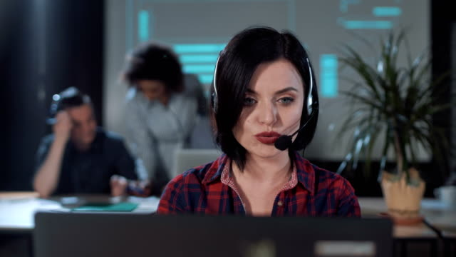 Operator talking to client Female operator in call center looking at camera and talking to a customer. saleswoman stock videos & royalty-free footage