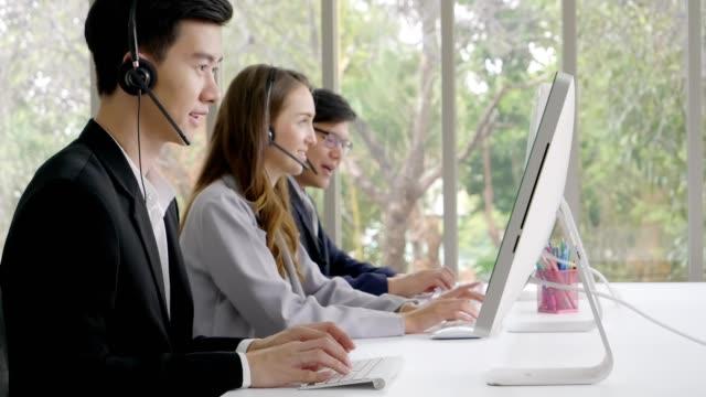 オペレーターチーム、クローズアップフェイスオペレータールームオフィスでの顧客サービスを話している人、コミュニケーション技術のコンセプト - 支えられた点の映像素材/bロール