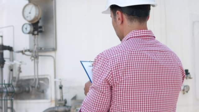 Operator with clipboard check parameters on instrumentation video