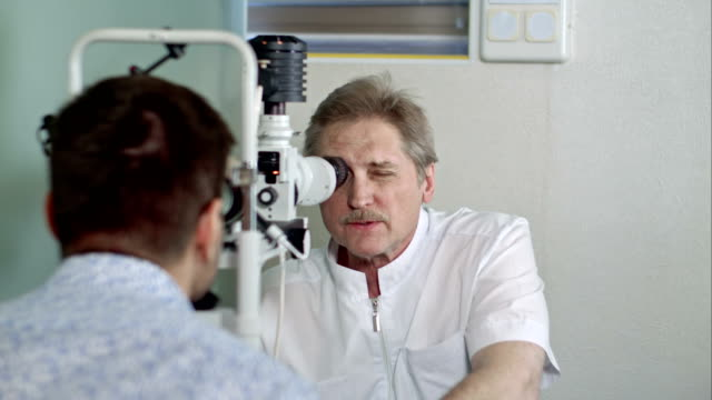 Ophthalmologist and young man checking eyesight in clinic video