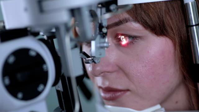 眼科医は、女性の目をチェックします。 - 検眼医点の映像素材/bロール