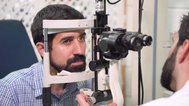 augenarzt überprüft jungen mann sehkraft - patient in der augenklinik. - ophthalmologe stock-videos und b-roll-filmmaterial