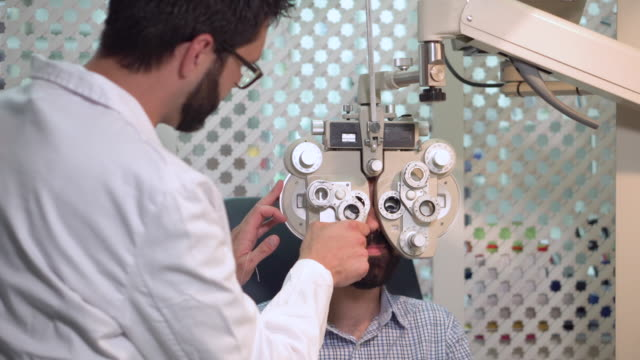 vidéos et rushes de ophtalmologiste examinant le patient avec le dispositif visuel d'inspection. mâle. patient pour vérifier la vision dans la clinique ophtalmologie. - rétine