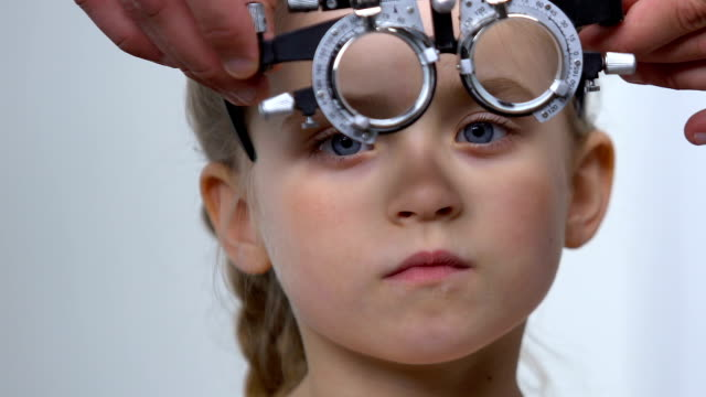 vidéos et rushes de ophtalmologiste aidant la petite fille mise sur le phoropter, diagnostic de contrôle de vue - réfracteur