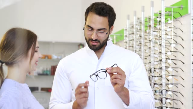 Optical Store. Eye Doctor Helping Woman Choosing Eyeglasses Optical Store. Eye Doctor Helping Woman Choosing Eyeglasses, Optician And Client eyesight stock videos & royalty-free footage