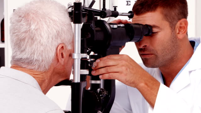 Optician examining a patients eyes video