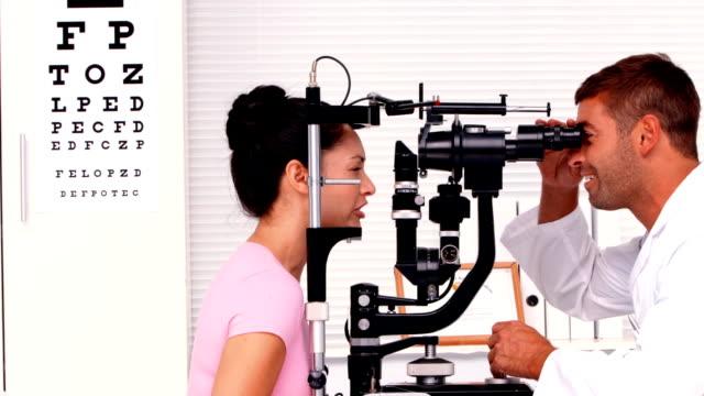 Optician examining a patients eyes video