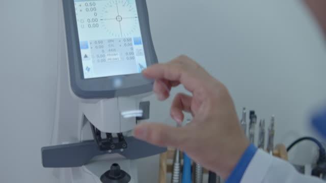 Optician measuring and preparing glasses