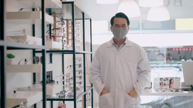 Optician organizing eyeglasses shelf - Stock Video video