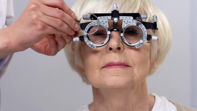 vidéos et rushes de optician mettant l'objectif dans le phoropter utilisant le patient féminin aîné, soins de santé - réfracteur