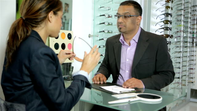 Optician shows sunglasses to client video